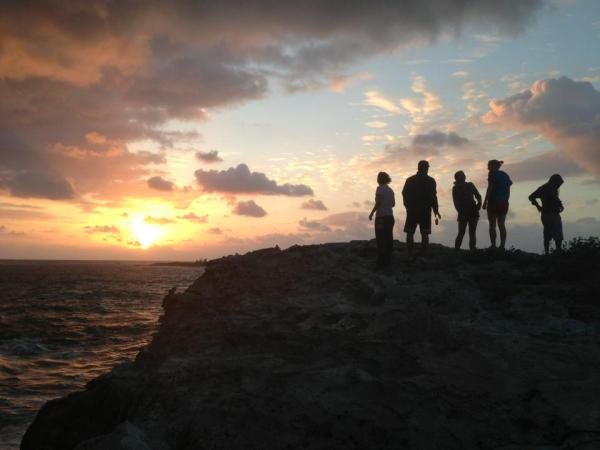 """On our last day on the island, some of us work up early, around 5:45, to go see the sunrise. We walked onto a part of the island called """"North Point."""" In this picture, the sun is just starting to rise as Hannah Friesen '13, Elijah Bowen '14, Kristen Mueller '15, Siri McCord '15 and Pha Lor '13 look out"""